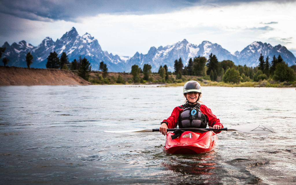 Abby in a kayak with the Tetons in the background.