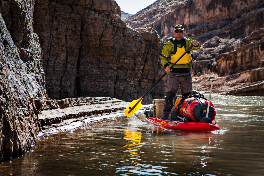 Peter paddleboarding the San Juan River among canyons.