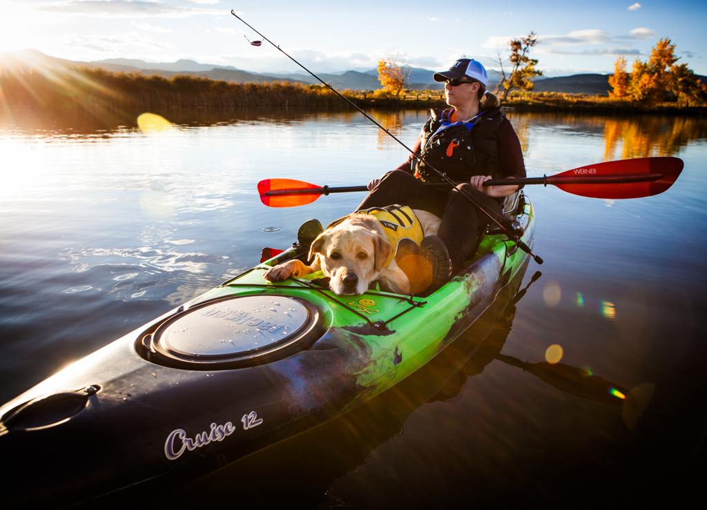 Kathy Holcombe kayak fishing in McCall Lake with dog on kayak with her.