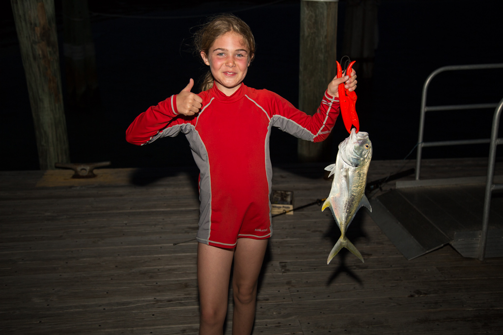 Abby showing a thumbs up while holding up a nice sized fish.