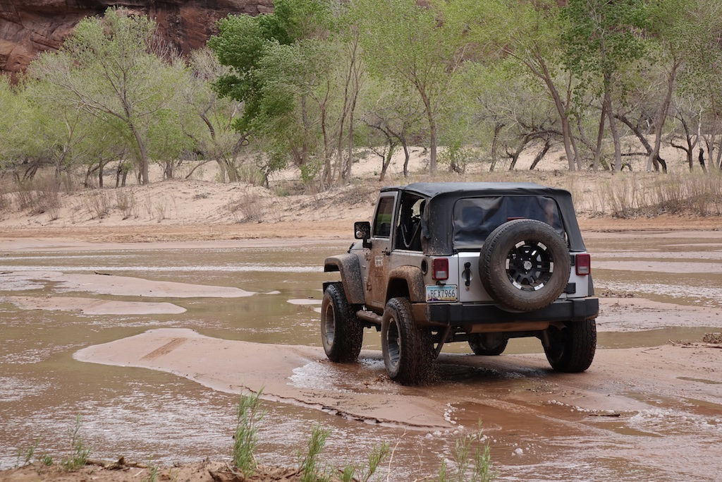 Jeep about to cross shallow stream.