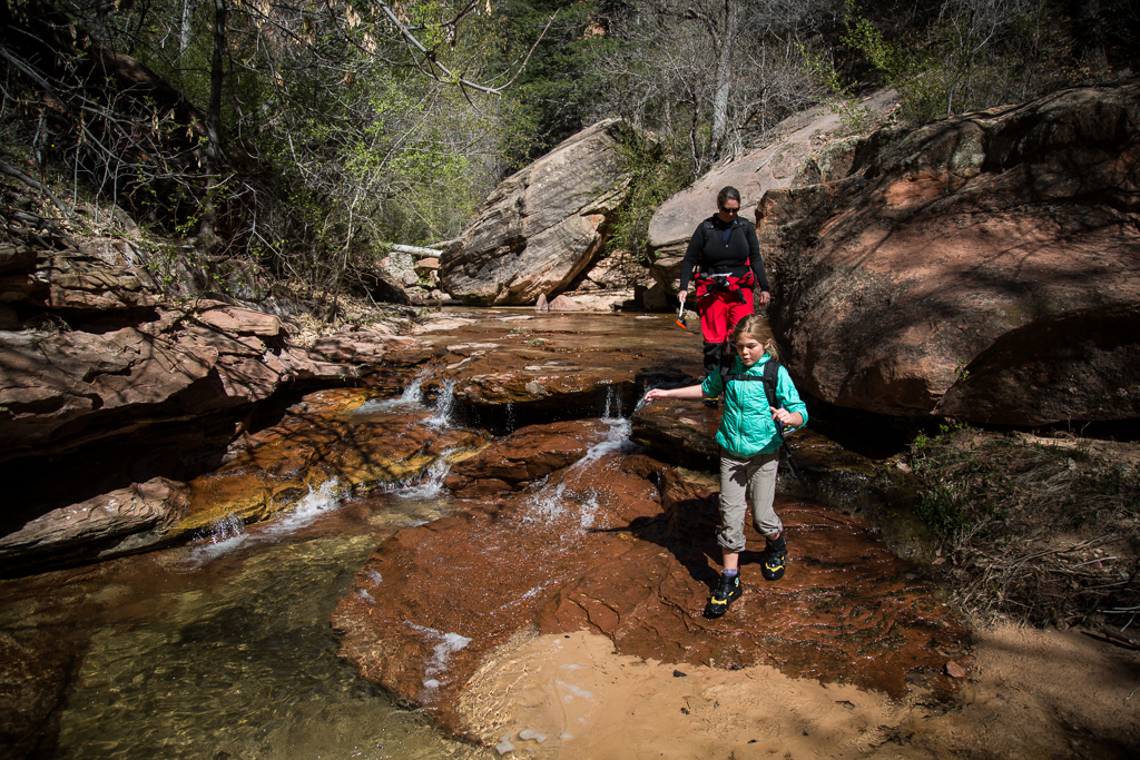 Abby and Kathy walking along the red rock ledges next to a spring.