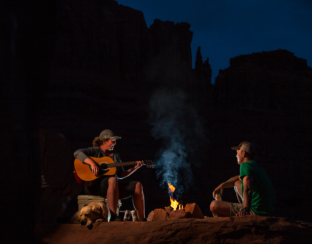 Kathy playing guitar next to campfire with yellow lab, Tucker, laying at her feet
