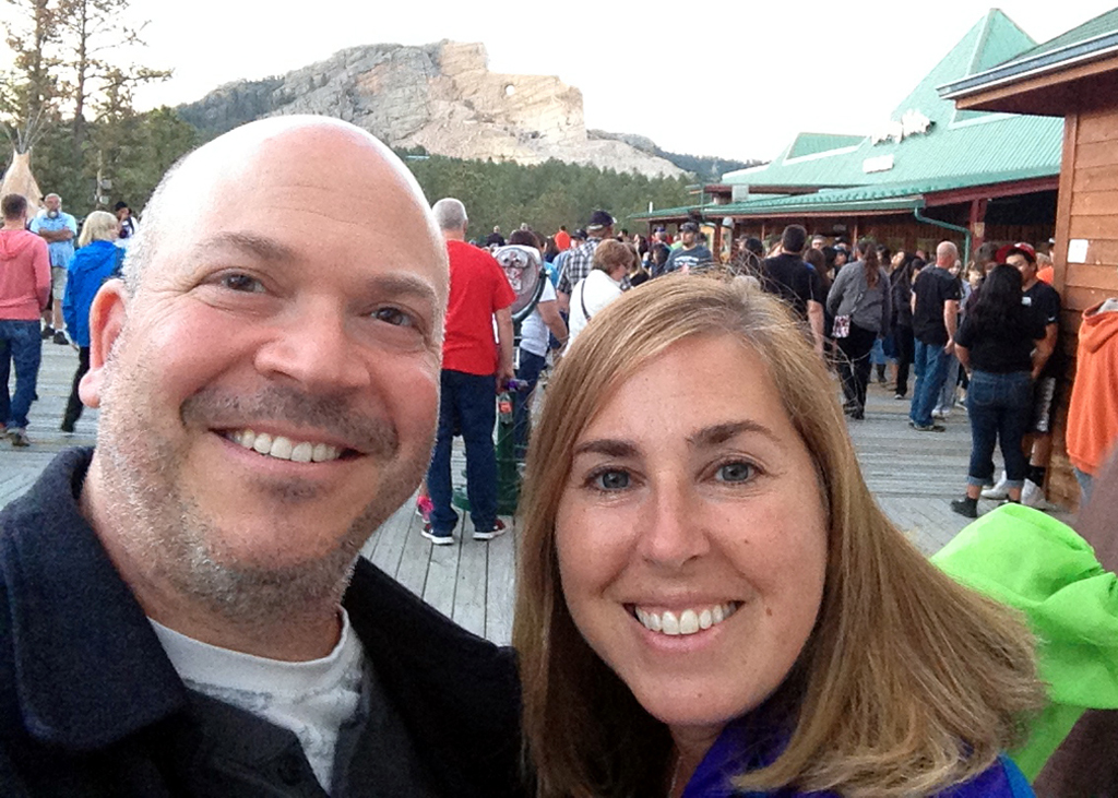Couple smiling with Crazy Horse Monument in the background.