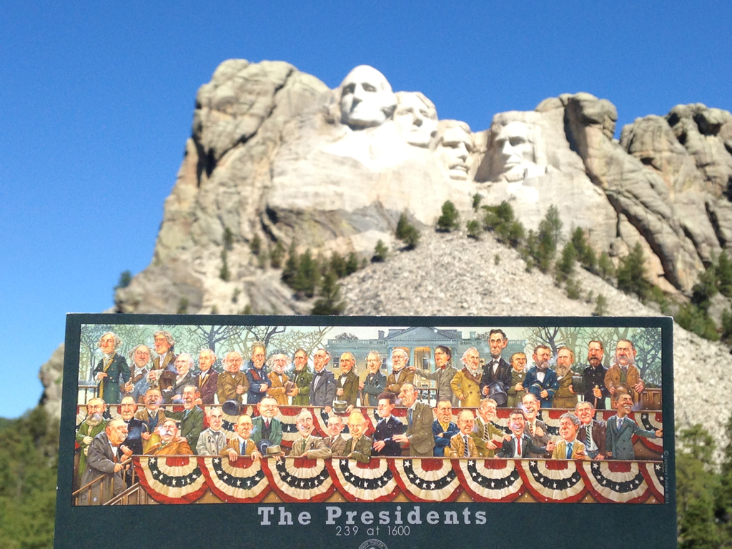 "Book ""The Presidents"" held in front of Mount Rushmore."