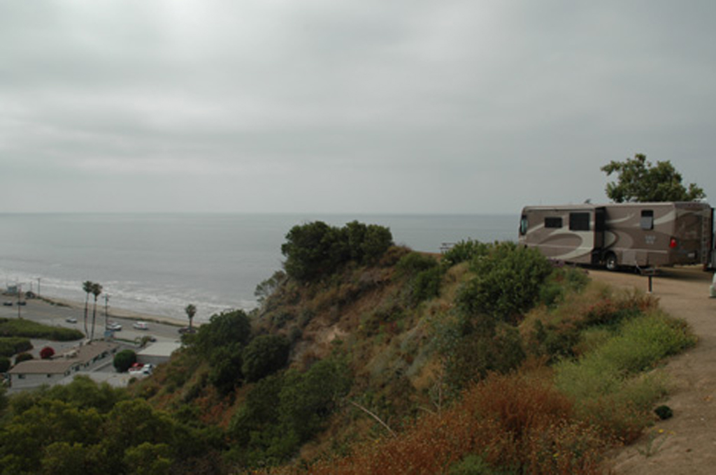 Winnebago motorhome parked in campsite on a hill overlooking road and ocean beneath.
