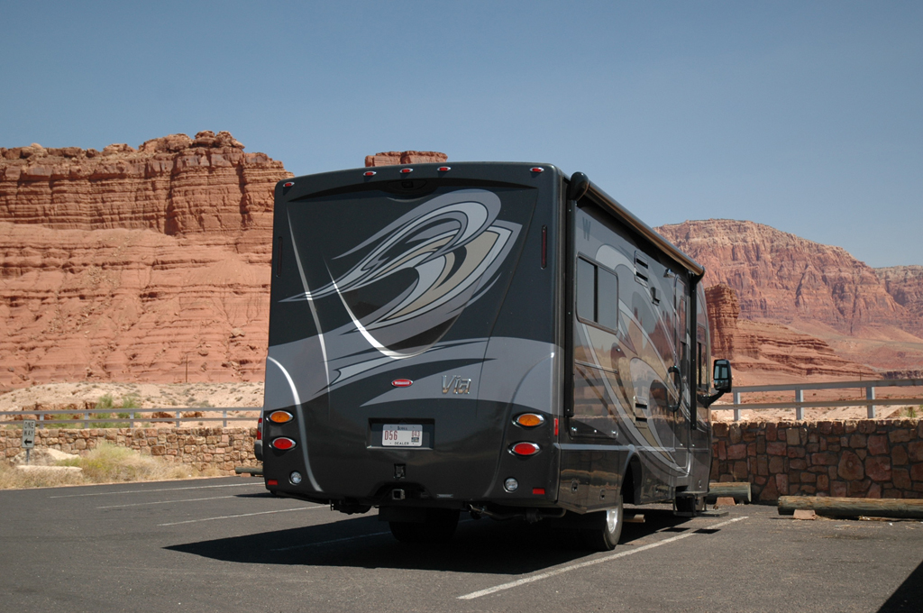 Winnebago Via in parking lot with red canyons ahead.