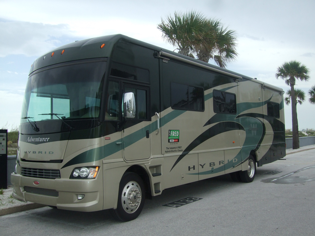 Winnebago Adventurer parked with palm trees along roadway.