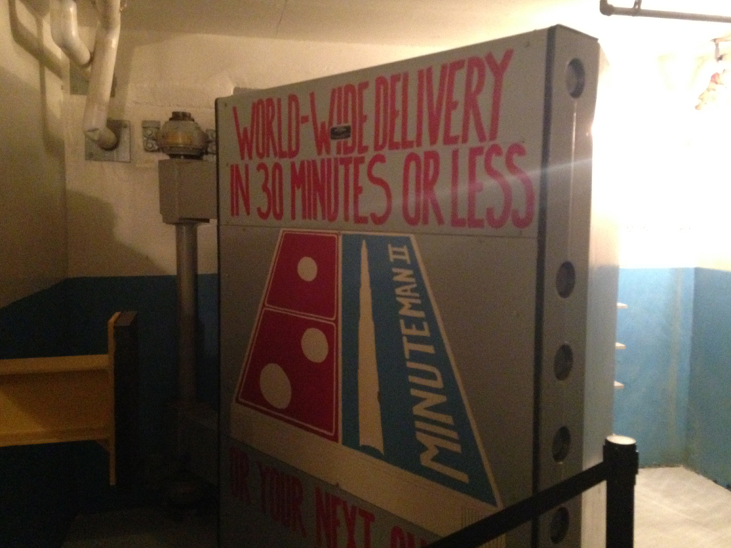 "Bomb shelter door that has been made to look like a pizza box that reads, ""World-Wide delivery in 30 minutes or less."""