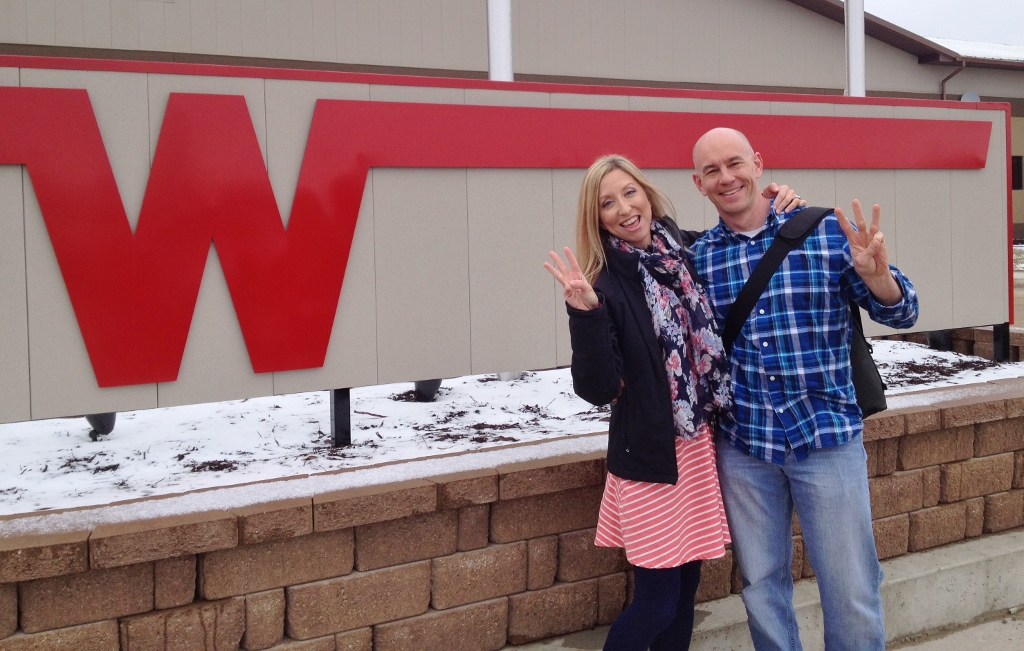 James and Stef standing in front of Winnebago sign.
