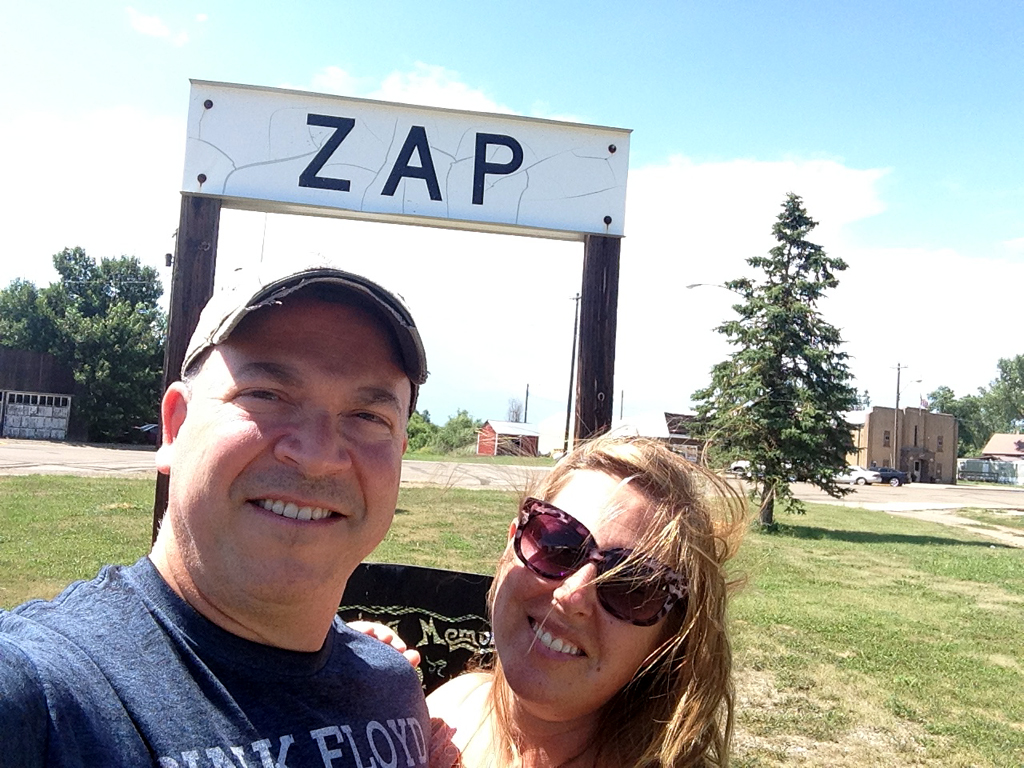 "Couple taking a selfie in front of ""ZAP"" sign."