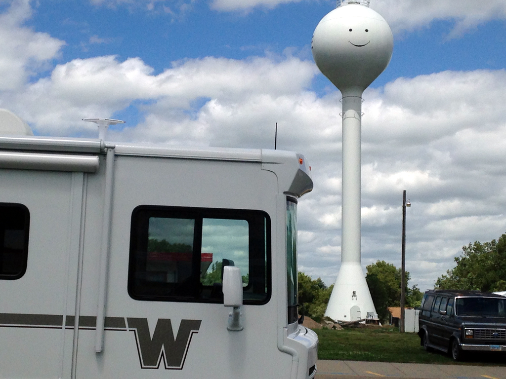 Winnebago motorhome parked in front of smiley face water tower.
