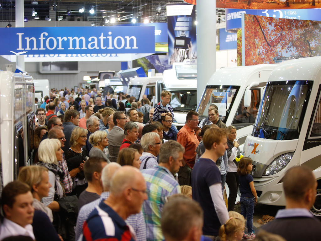 Crowd of people gathered among RVs at Caravan Salon 2014.