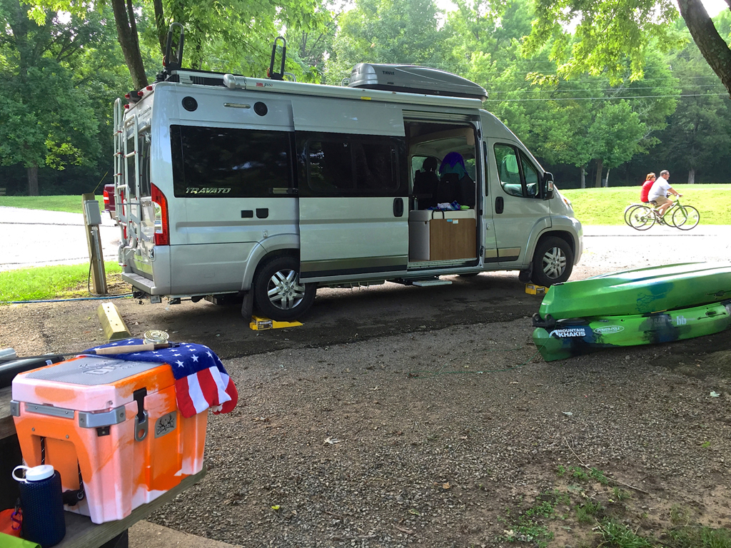 Travato on side of road with slide door open and kayaks and cooler on the ground outside