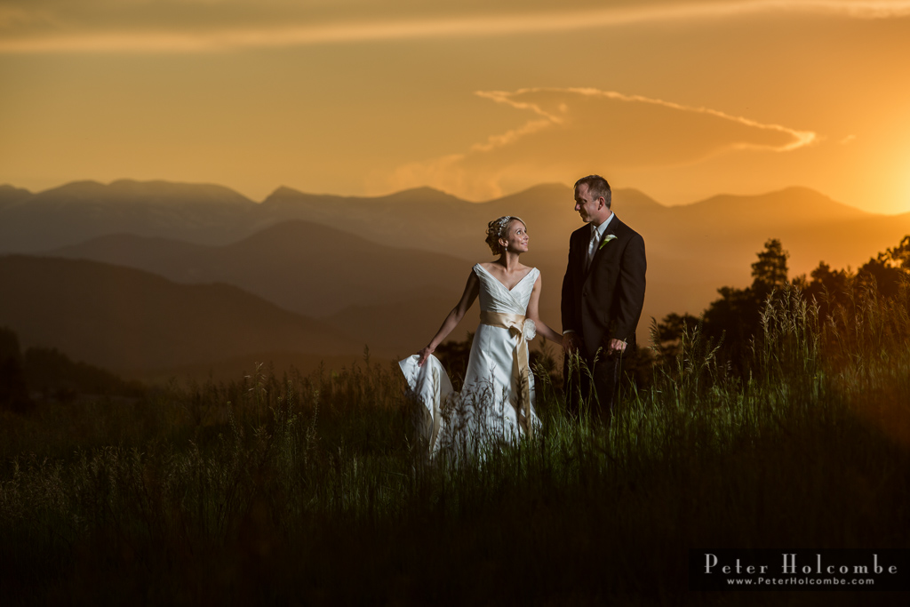 Couple in wedding attire with mountains and magnificent sunset in the background.