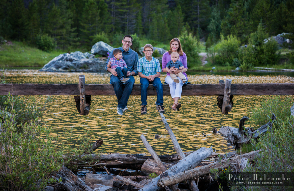 Family of 5 sitting on a log over the water with pine trees in the background.