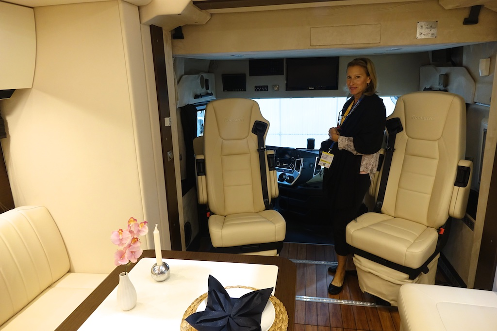 Woman standing at the front of a classy Class A motorhome.