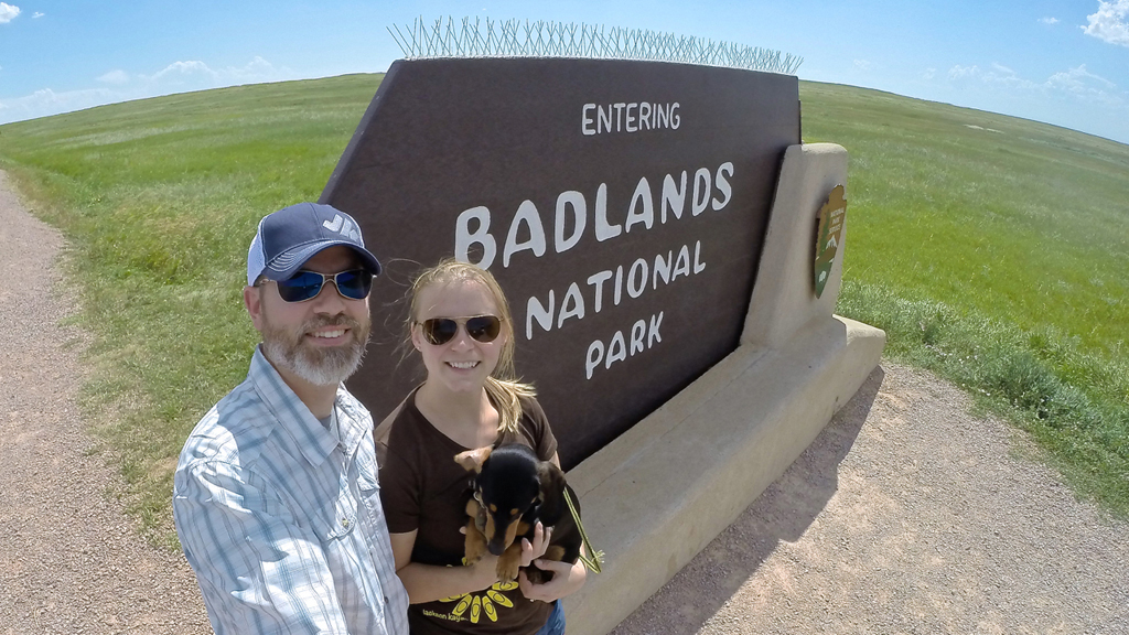 Couple and dog next to sign for Badlands National Park.
