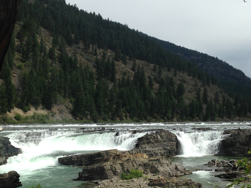 Kootenai Falls at the base of a tree covered hillside.