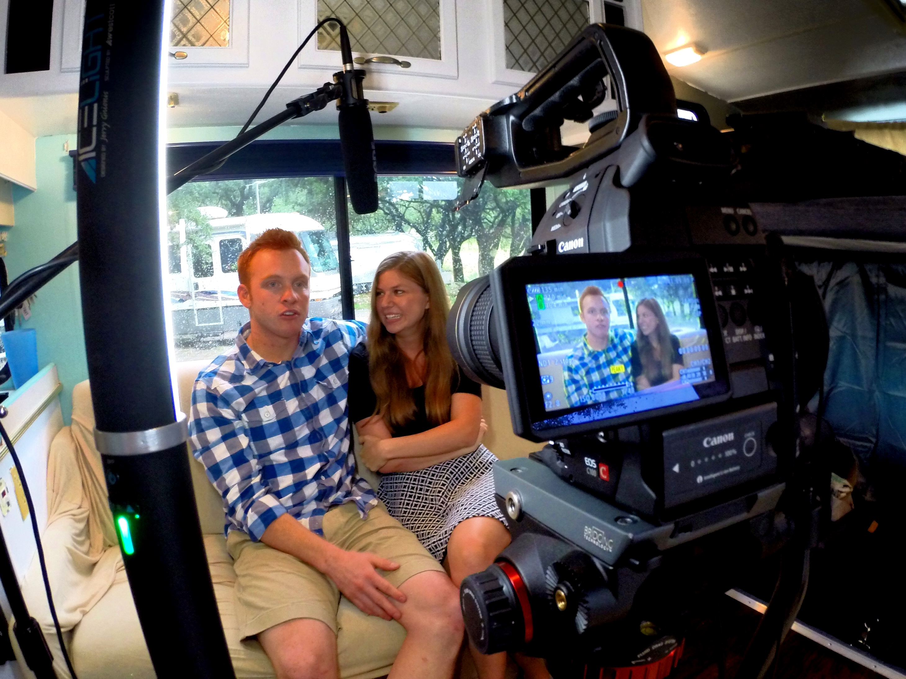 Heath and Alyssa on couch of RV with camera filming them.