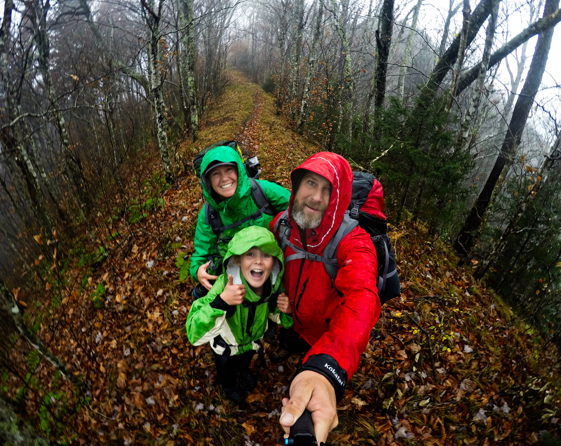 Family taking selfie on leaf covered trail with bare trees and fog surrounding.