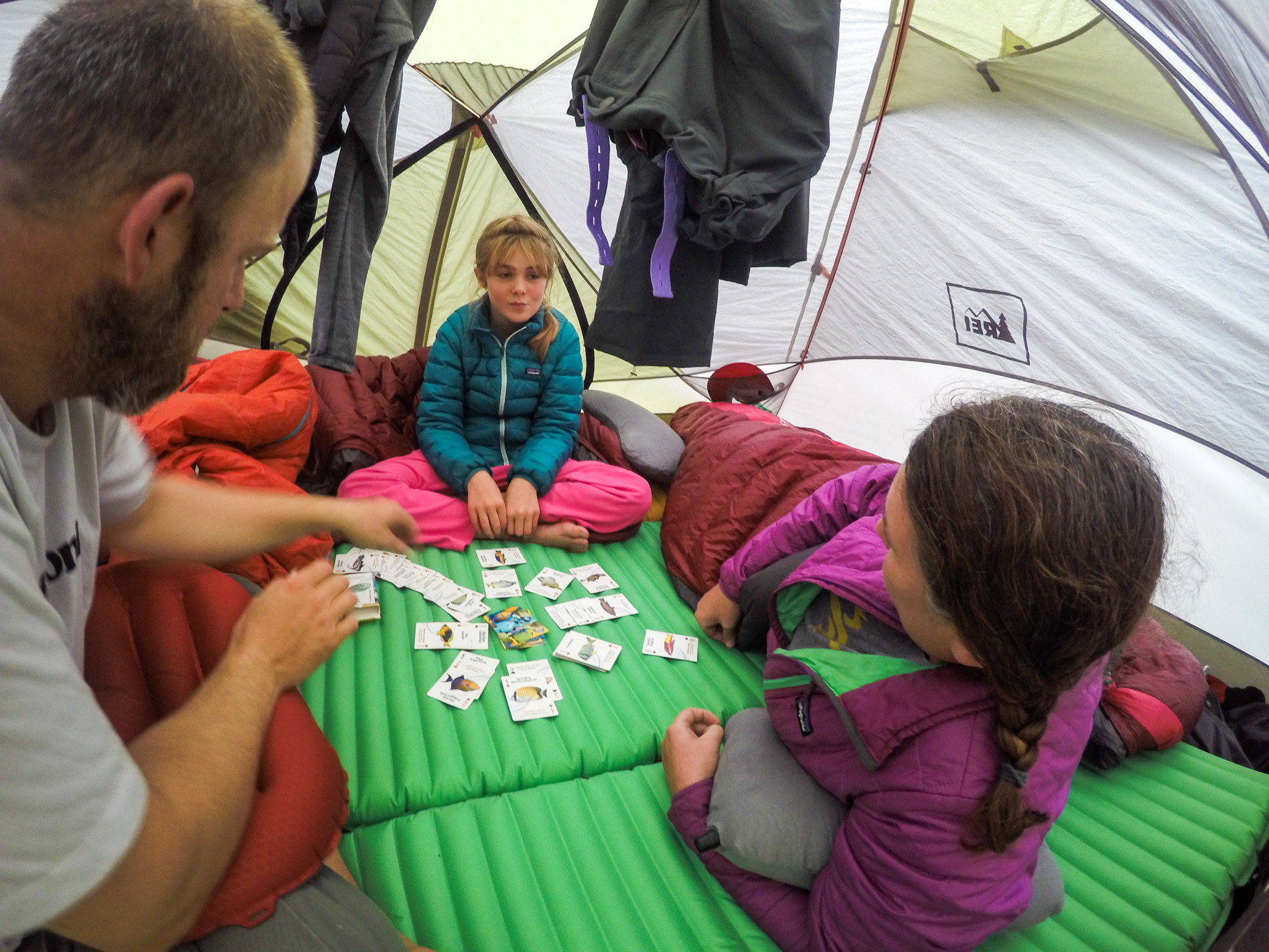 Family in tent playing a card game.
