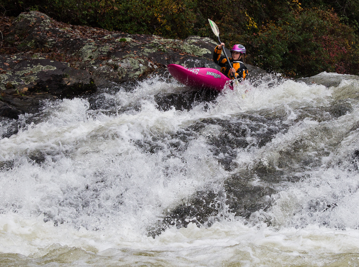 Girl going over rapid in a hot pink kayak.