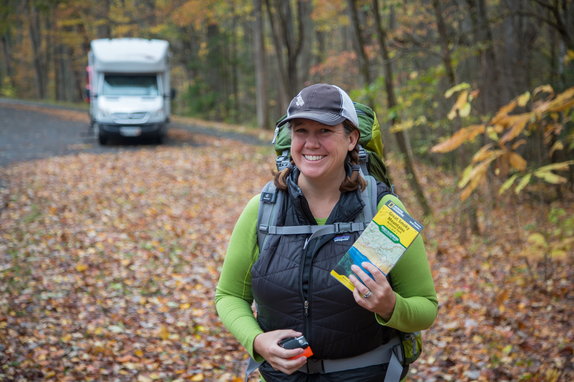 Woman smiling while holding Great Smoky Mountains map with Winnebago View parked in the background.