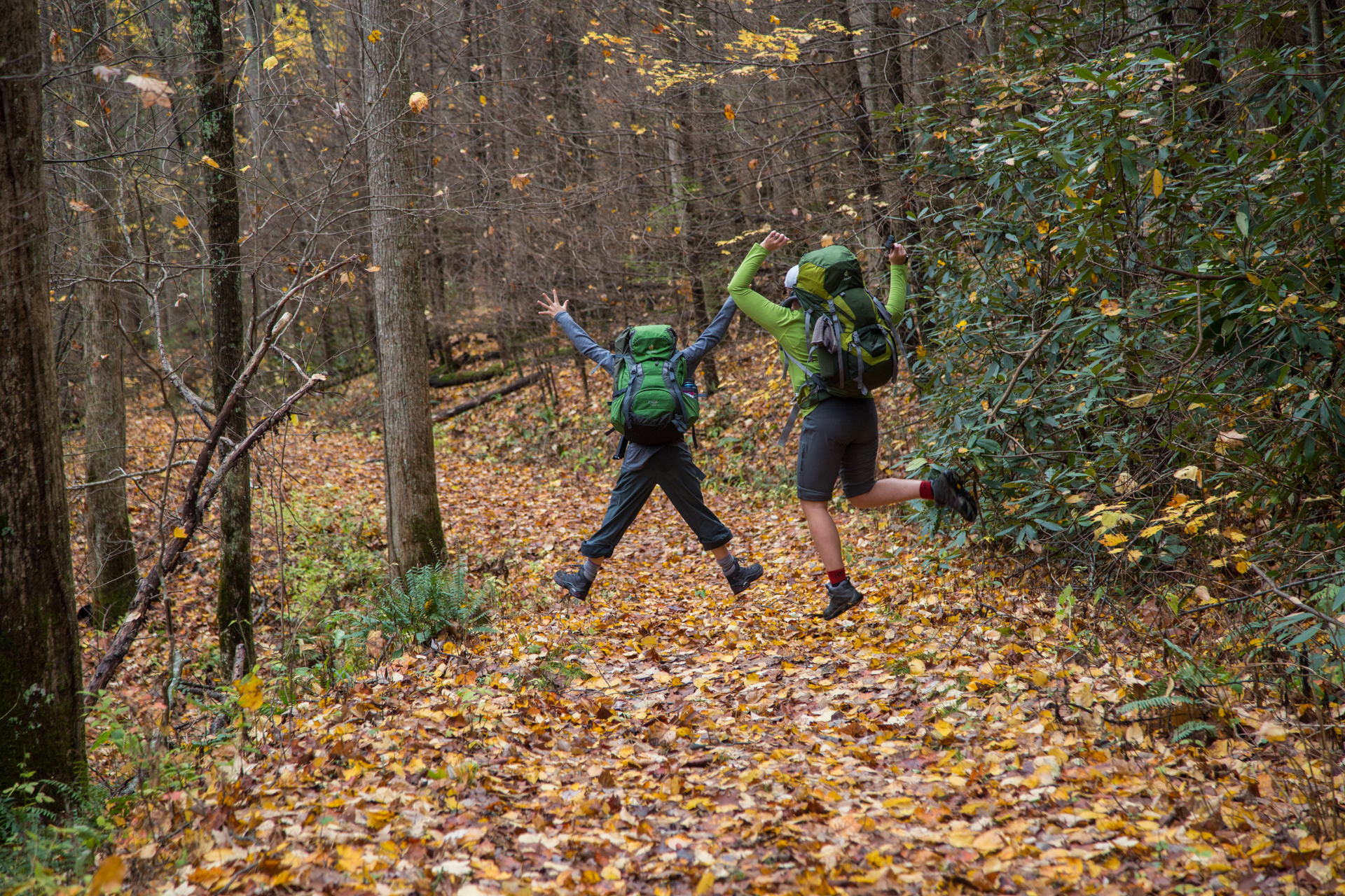 Two ladies with hiking gear jumping in the air on leaf covered trail.