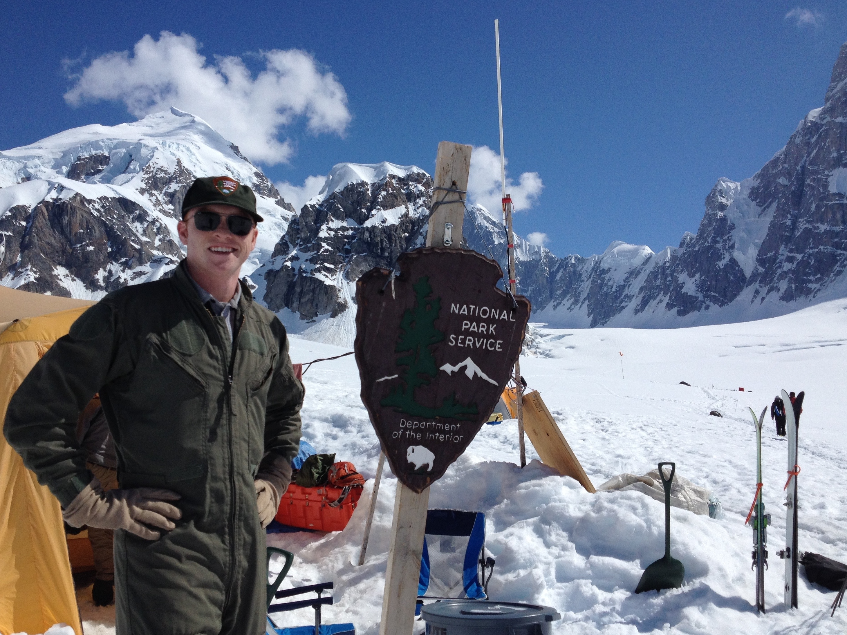 Heath on snow covered mountain next to sign for National Park Service Department of the Interior.