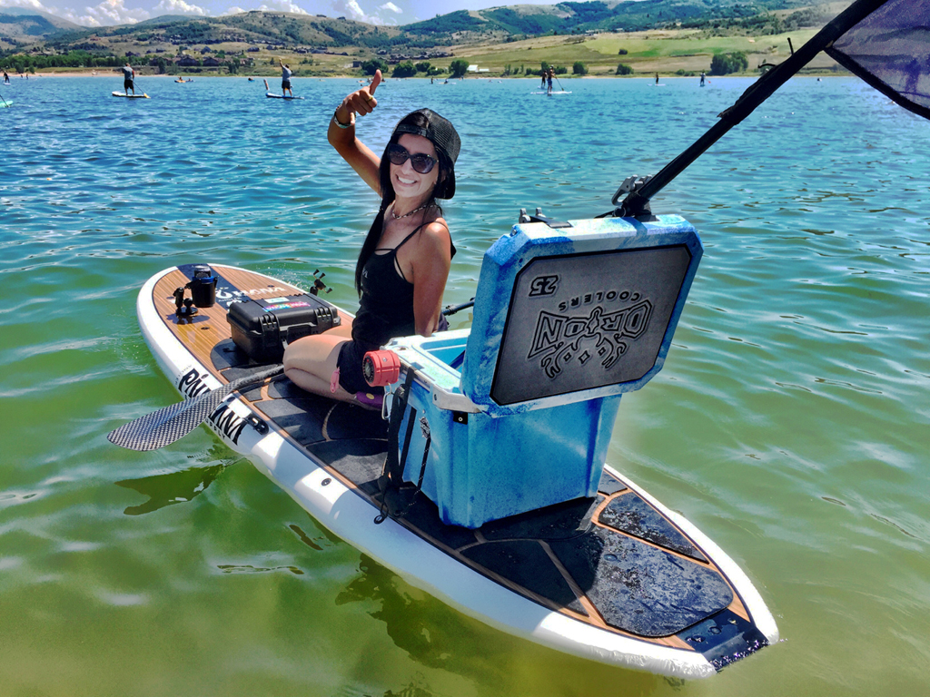 Woman on a paddle board with Orion cooler.