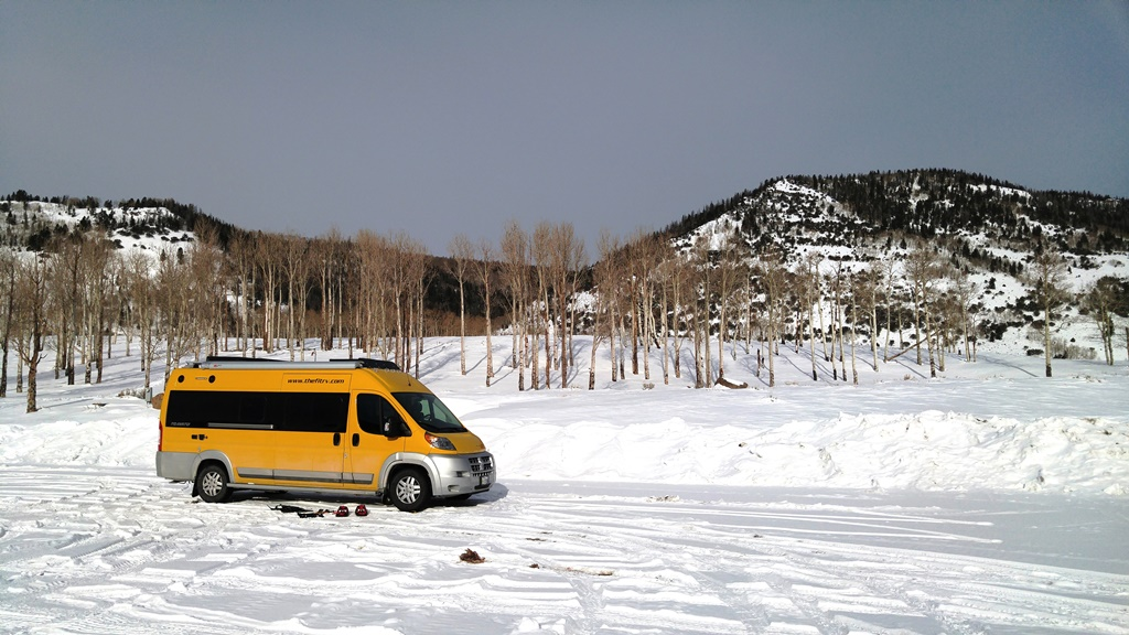 Yellow Winnebago Travato parked on snow covered road with hills behind.