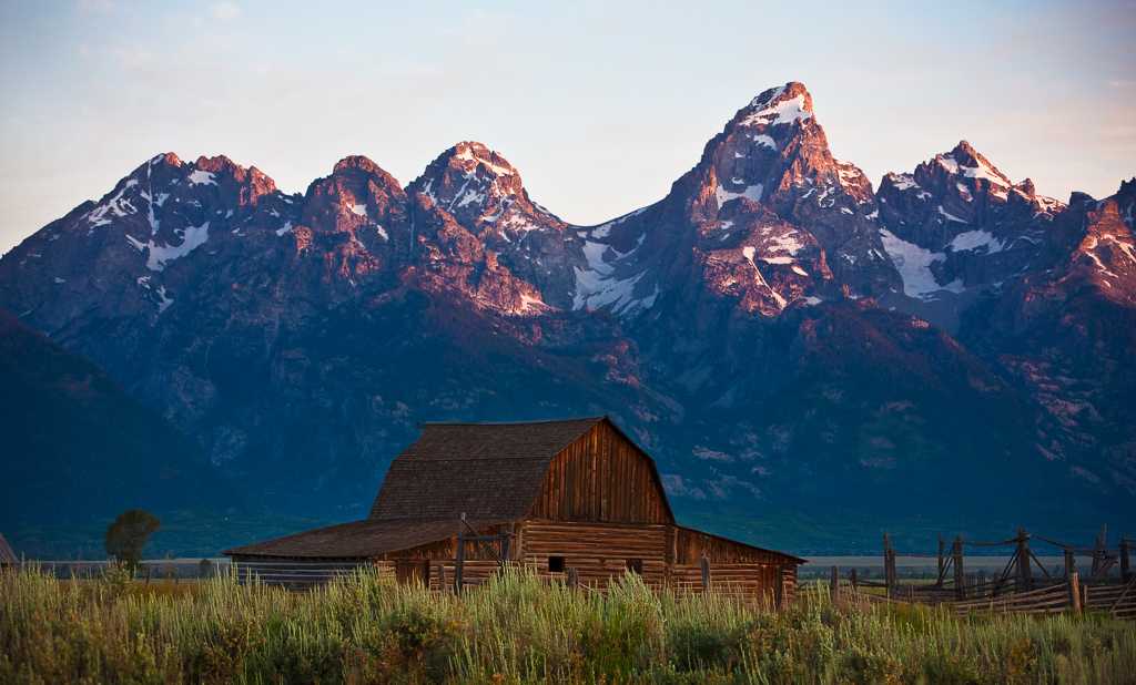 Morning light hitting the top of the Grand Tetons with log building in grassy field below.