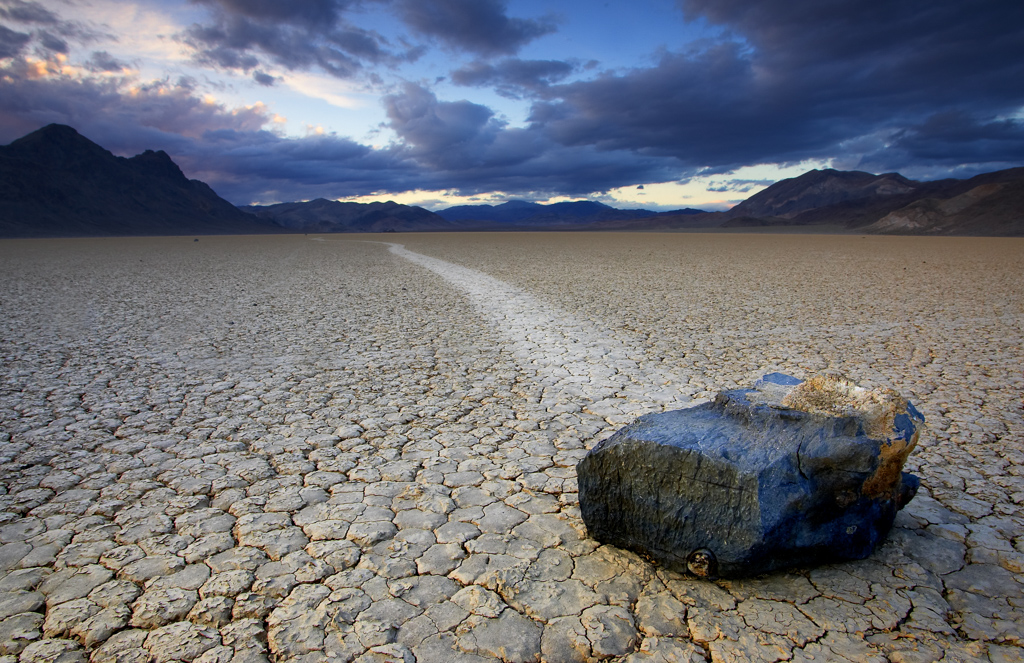 Rock in middle of dry ground with mountains in the distance.