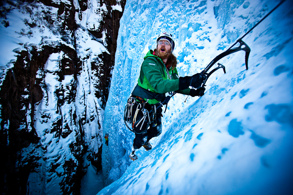 Man climbing icy cliff-side.