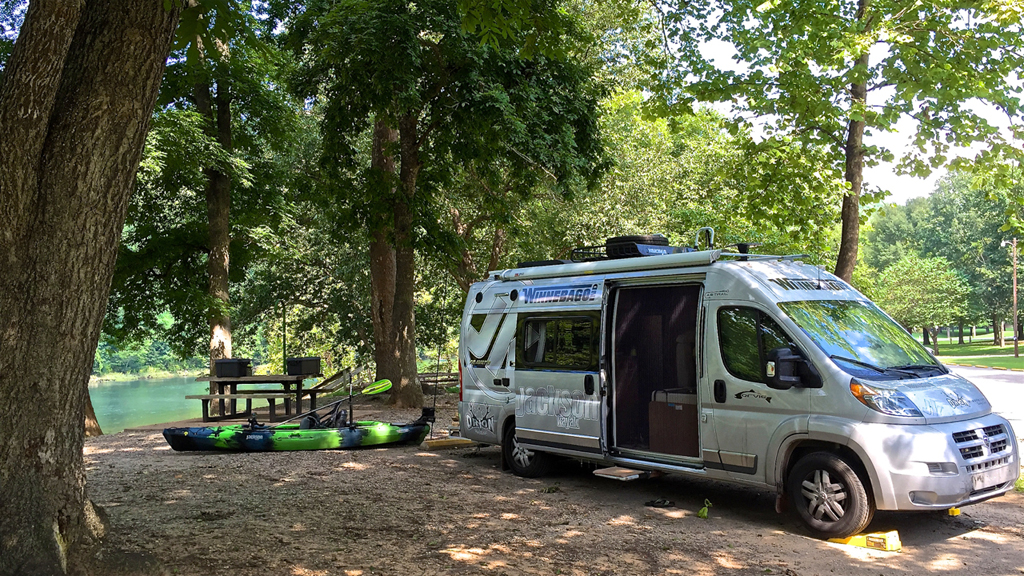 Winnebago Travato parked in campsite covered by trees and next to a river.