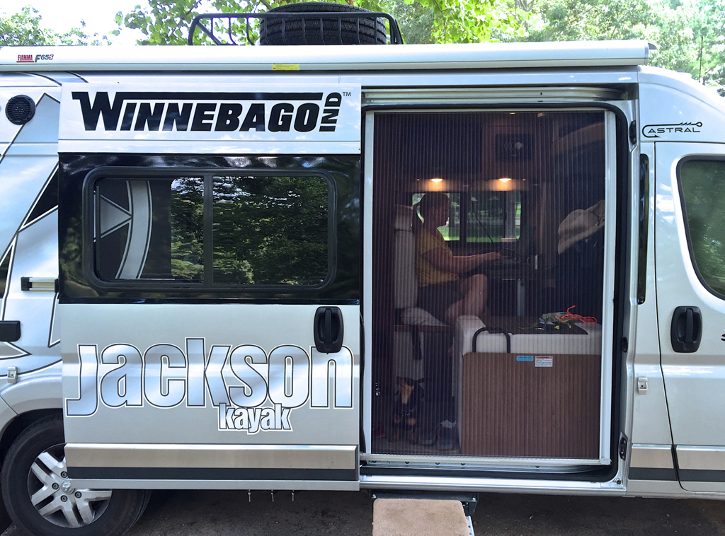 Winnebago Travato with sliding door open and a screen covering the opening.