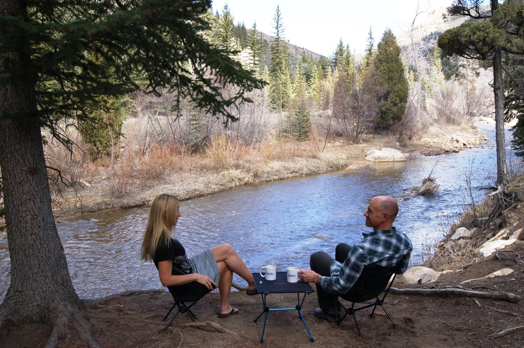 James and Stef sitting along the river in camping chairs with table between them.