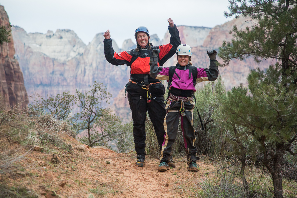 Kathy and Abby with arms raised in victory as they step back out to the top of the canyon.