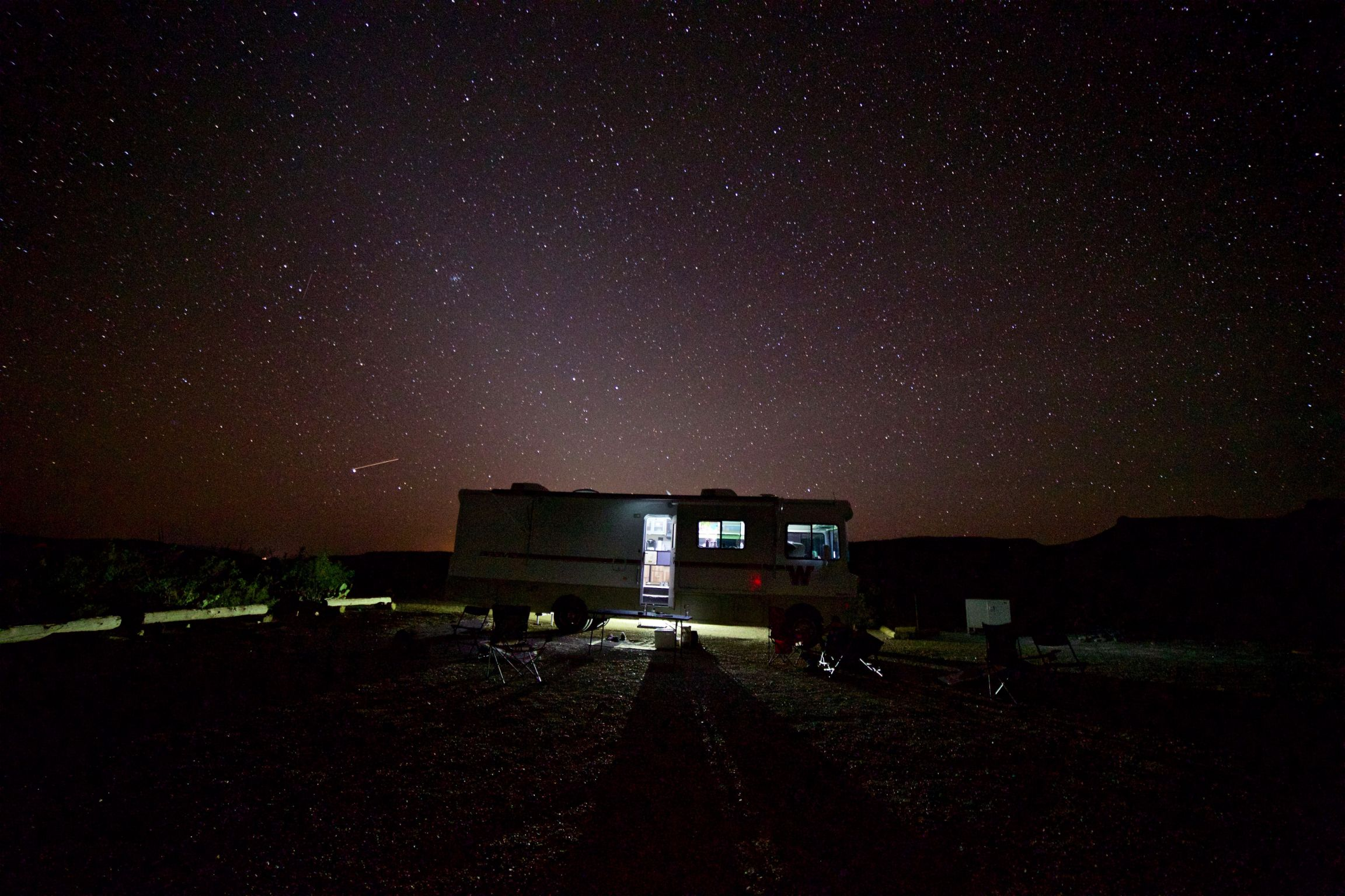 Winnebago Brave parked in the desert with a star filled night sky above.