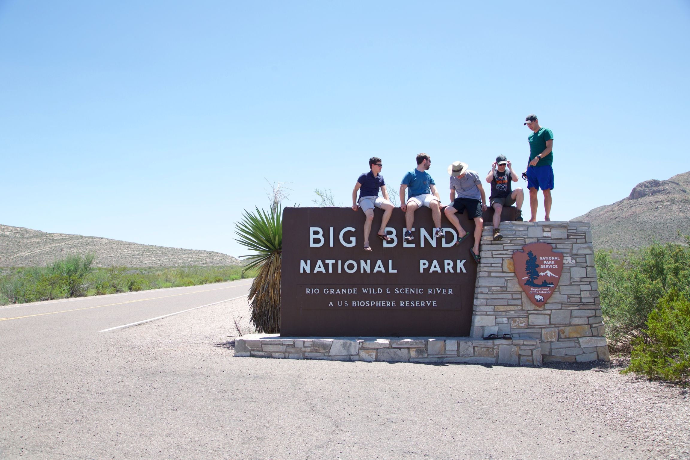 Group of five sitting atop the Big Bend National Park sign.