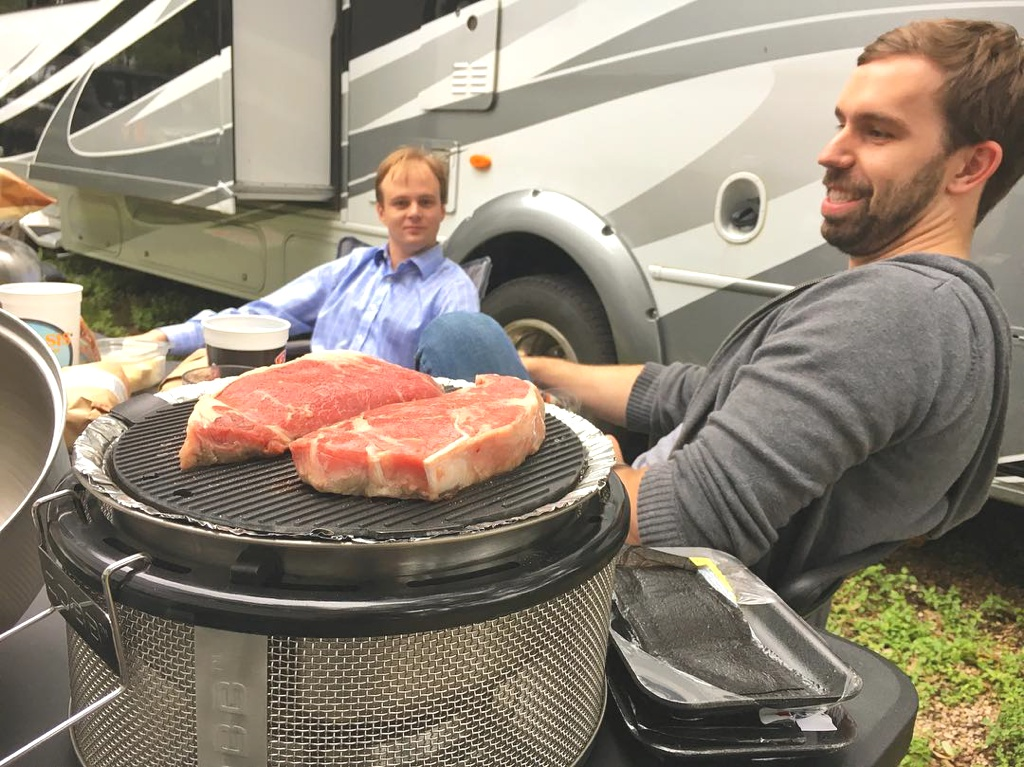 People sitting outside RV with meat being cooked on a small grill.