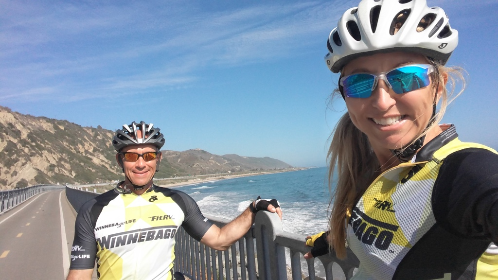 Stef and James taking a selfie on a bike path along the water.
