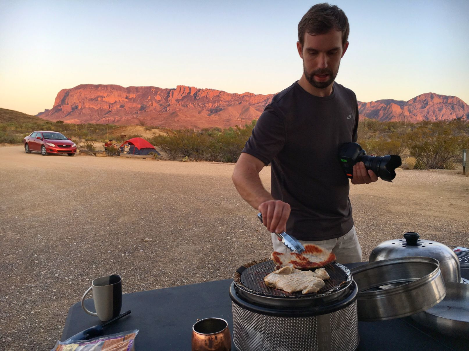Man grilling with other campers and the mountains in the background.