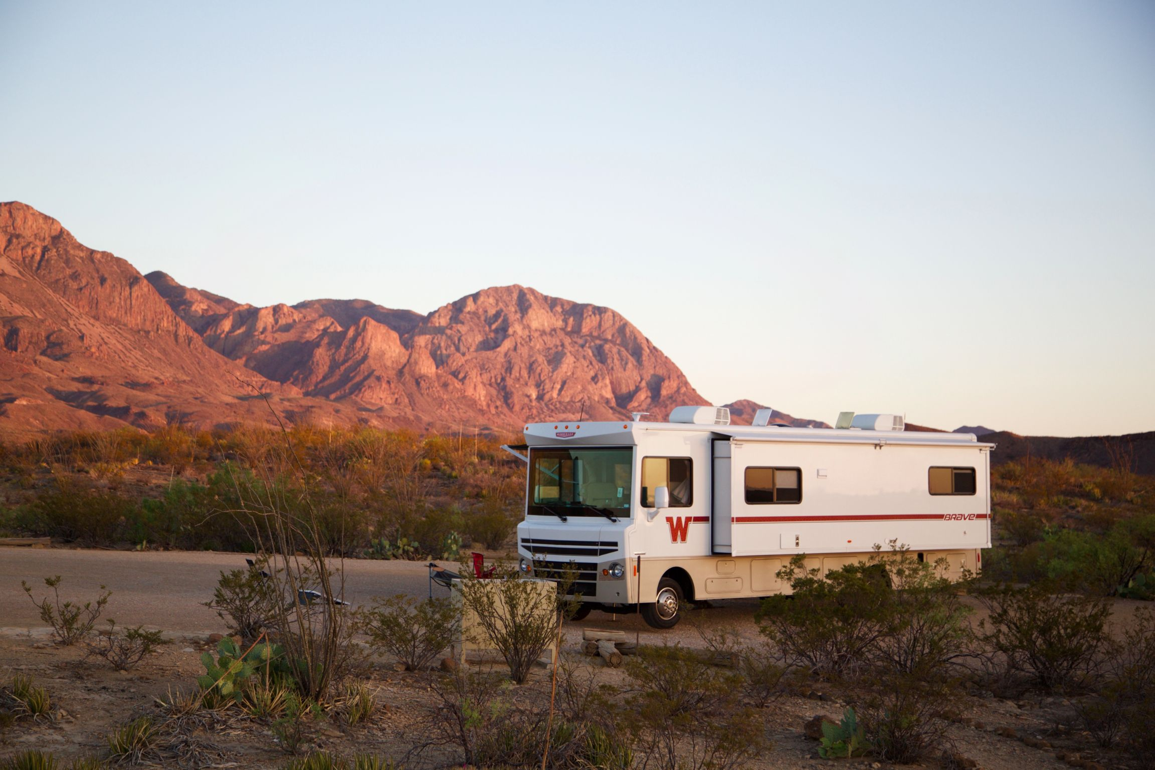 Winnebago Brave parked in desert landscape campsite with mountains in the background.