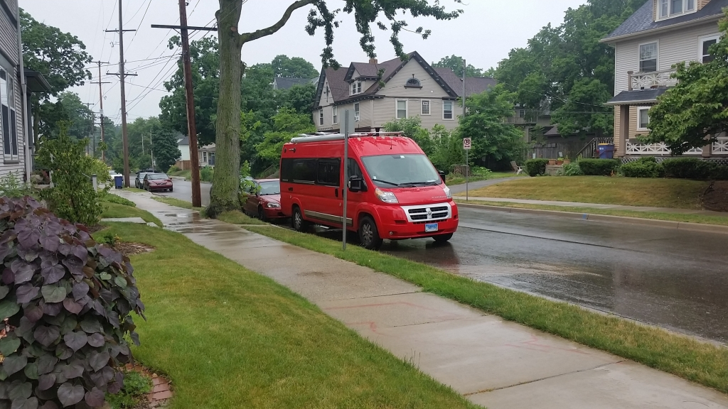 Red Winnebago Travato parked on a residential street.