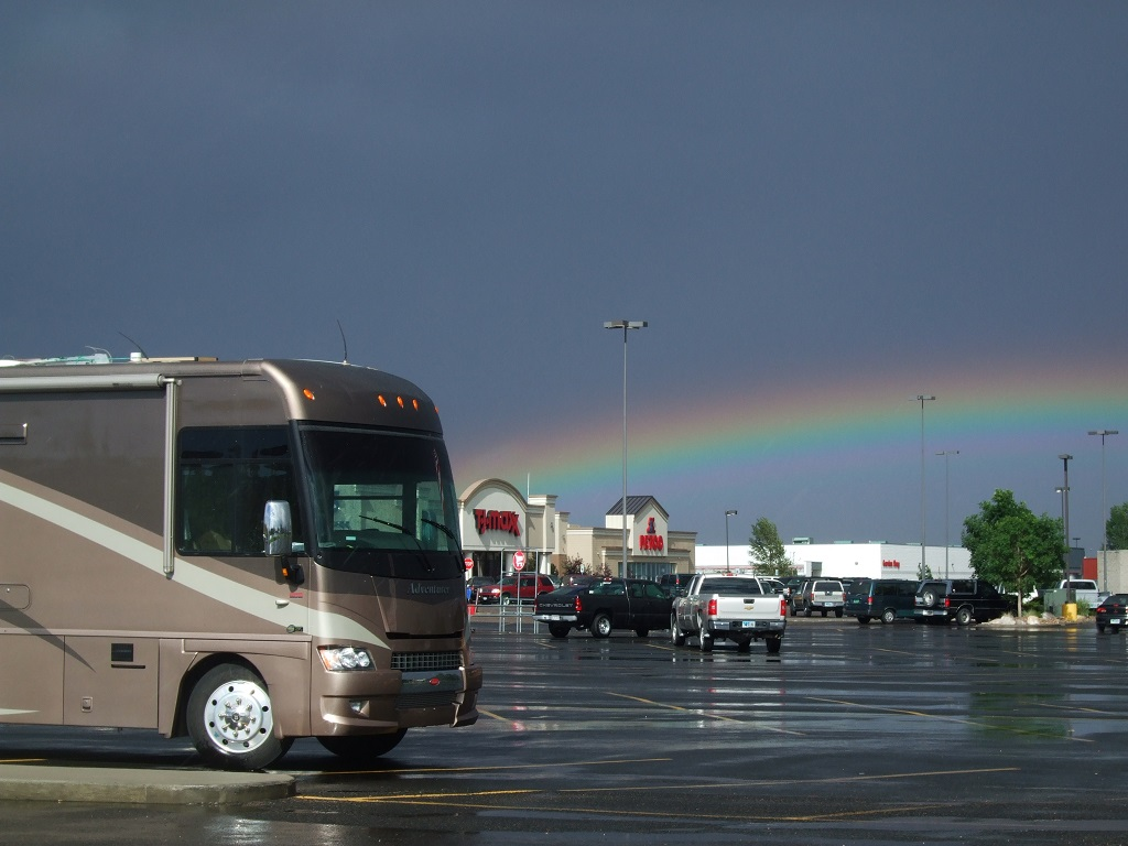 Winnebago parked in parking lot, with rainbow overhead.