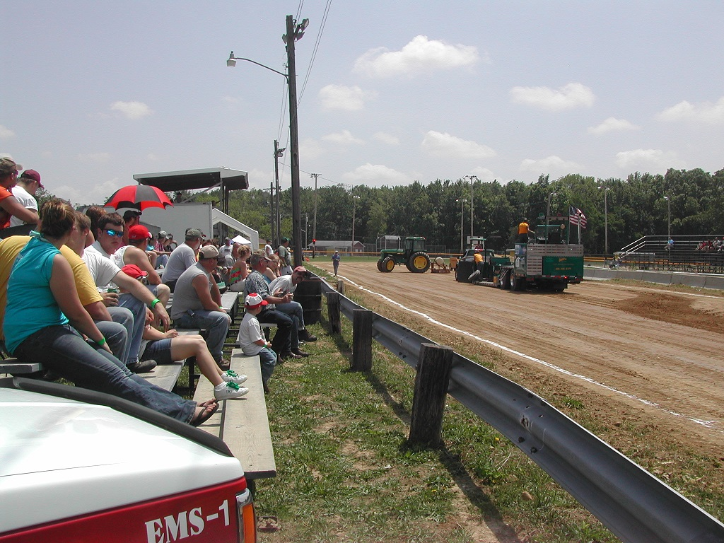 Crowd watching tractors on a dirt track.
