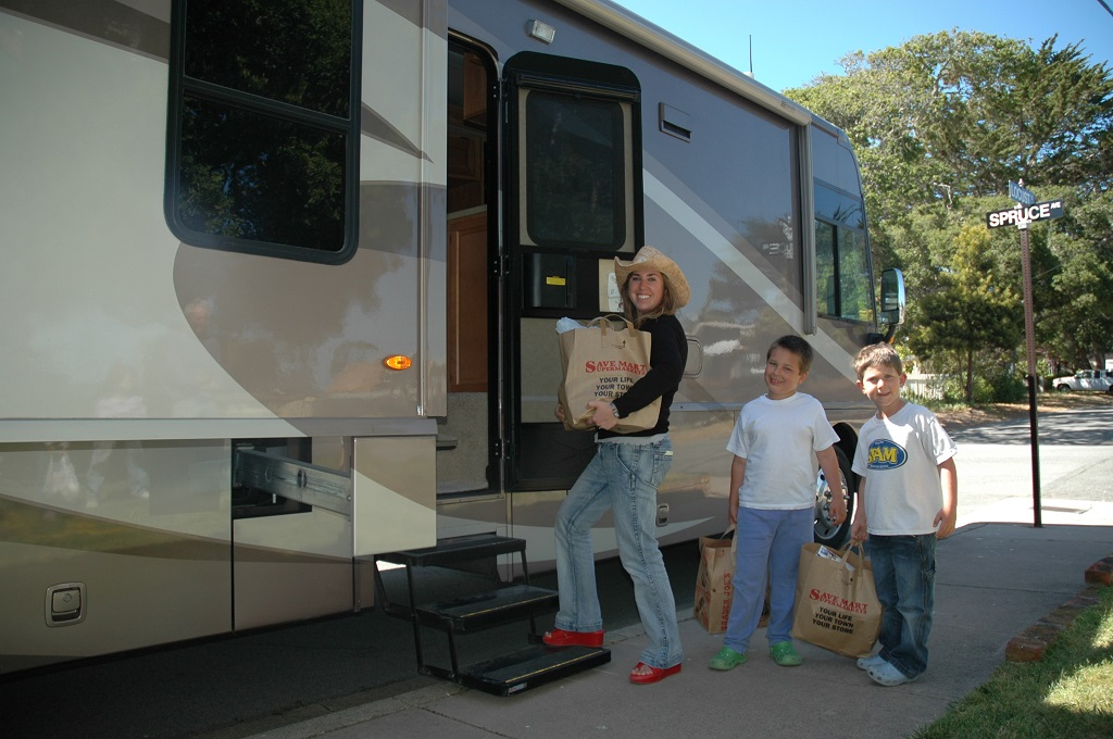 Woman and toy boys heading into their RV with grocery bags.