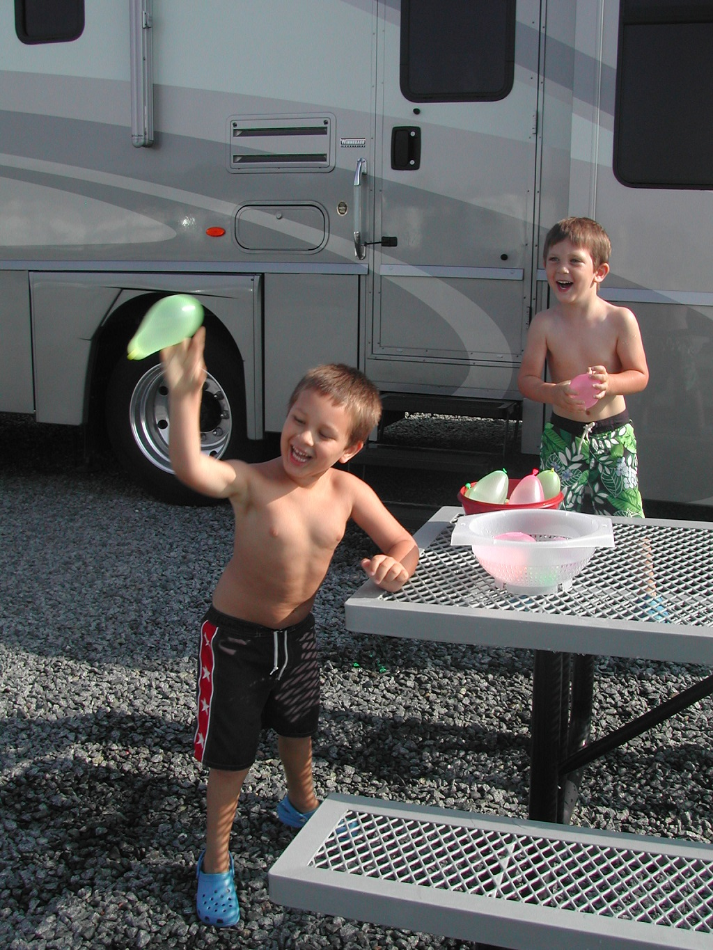Two boys playing with water balloons outside motorhome.